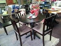 round brown wooden table with four chairs dining set