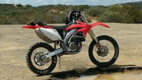 red, white, and black motocross dirt bike