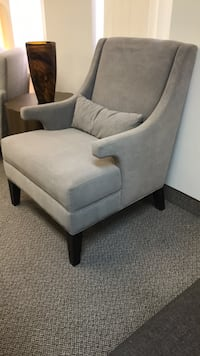 Gray suede sofa chair with throw pillow