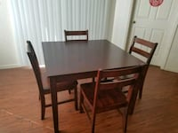 rectangular brown wooden table with four chairs di College Station, 77840