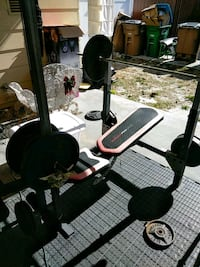 black and red bench press and barbell stand