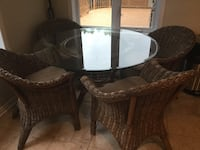round clear glass top brown wooden base table and brown wicker armchairs La Prairie, J5R