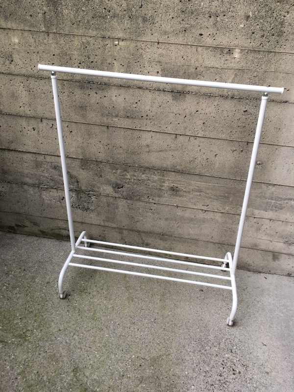 white metal rolling clothes rack