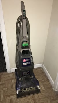 Black and grey upright carpet cleaner