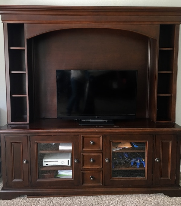 Brown wooden entertainment center. Tv not included