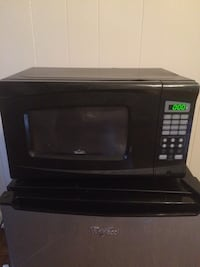 black Rival digital microwave oven and grey Whirlpool compact refrigerator