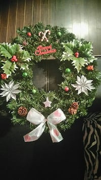 white and green poinsettias and mistletoe accent pine wreath