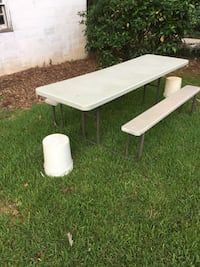 white plastic picnic table with two 5 gallon bucket's for end chairs