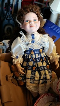porcelain doll wearing blue and white dress