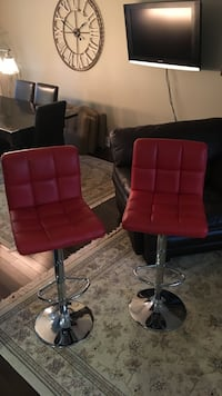 two stainless steel based red leather quilted bar stools