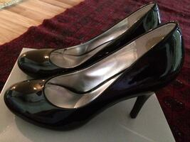 Black patent leather pumps on box