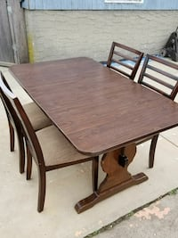 rectangular brown wooden table with four chairs di