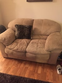 Brown fabric loveseat with throw pillow