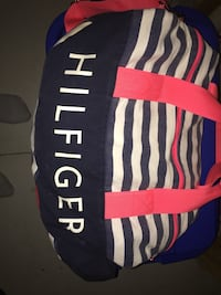 red, white, and black striped Tommy Hilgiger duffel bag