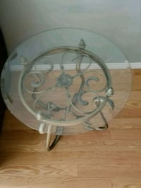 round clear glass top table with gray metal base London