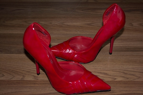 pair of red patent leather pointed-toe pumps