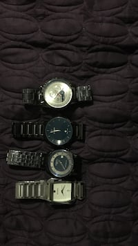 four silver-colored analog watches with link bracelet