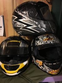 three assorted color full-face helmets