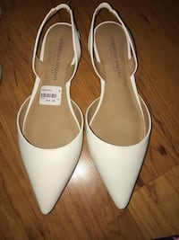 pair of white pointed-toe heeled shoes