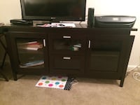 brown wooden TV stand with flat screen television