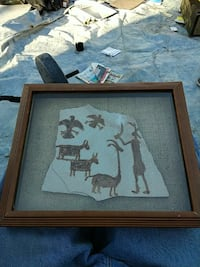 painting of man in front of animals with square brown wooden photo frame