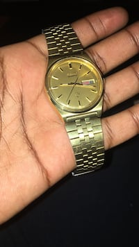 round gold-colored Seiko analog watch with link strap