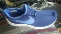unpaired blue and white Nike sneakers