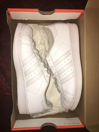 Pair of white adidas superstar sneakers with box