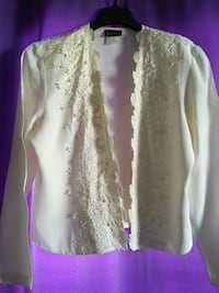 This ivory, embellished with pearls, blouse is open in the front.