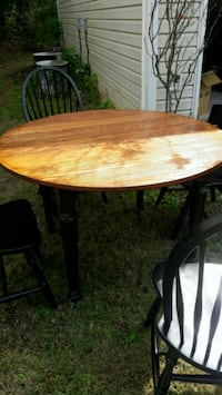round brown wooden table with black metal base Lawrenceville, 30045