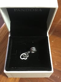 silver-colored Pandora pendant with white box