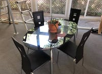 Modern glass and metal table, and 4 leather chairs. Almost new condition. Fairfax, 22031