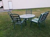 round black metal patio table with four chairs