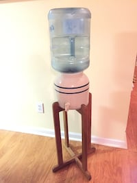 Porcelain water cooler with wooden stand and a 5-gallon bottle.
