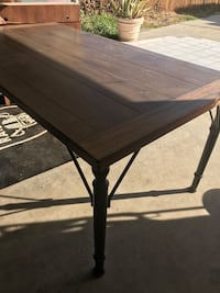 rectangular brown wooden table with black metal base