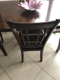Rectangular brown wooden table with four chairs dining set.