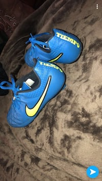 Pair of blue nike soccer cleats and shin pads  Clinton, 37716