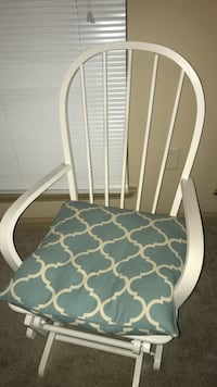 White wooden-frame windsor-back armchair with blue and white reverse moroccan tile print cushion