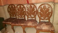 four brown wooden framed brown padded chairs