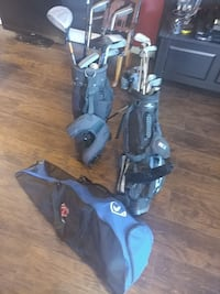 Two black golf bags with golf clubs and baseball