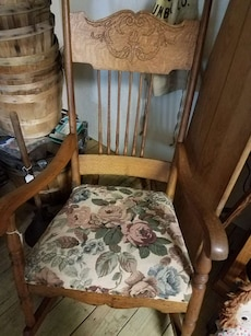 brown wooden rocking chair with white and red flor