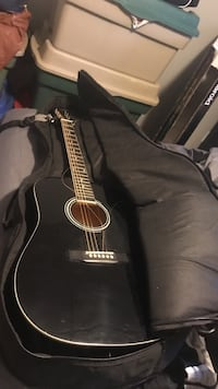 Black dreadnought acoustic guitar with accesories