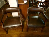 two brown wooden framed brown leather padded armch