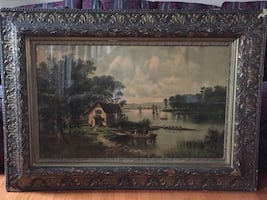 House near body of water framed painting