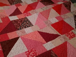 58x43 Hand made quilt mainly reds and pinks. Great for a sofa throw.