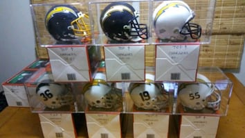 San Diego/LA Chargers Authentic Mini Helmets in display cases.