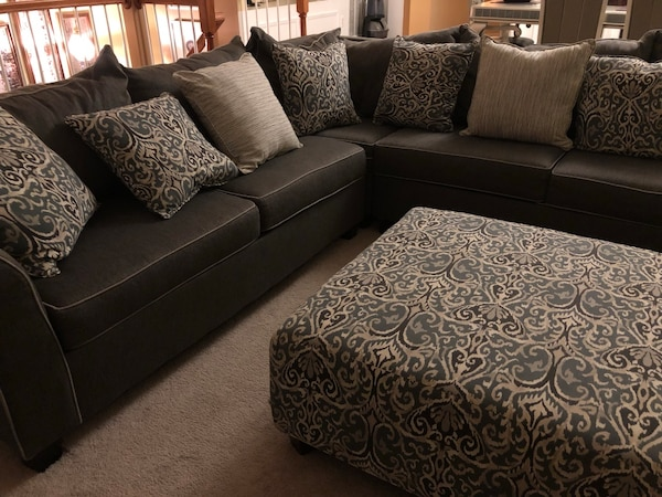 Gray sectional sofa with throw pillows and ottoman