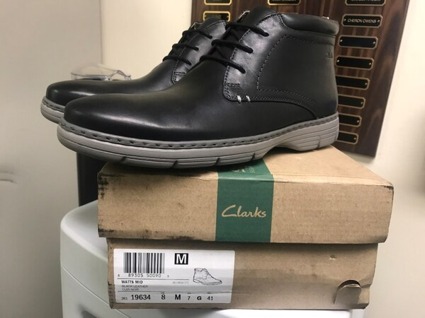 unpaired black leather work boot