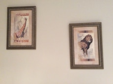 Giraffe and lion paintings in brown wooden frame