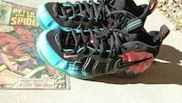 pair of black-and-blue Nike Foamposite shoes